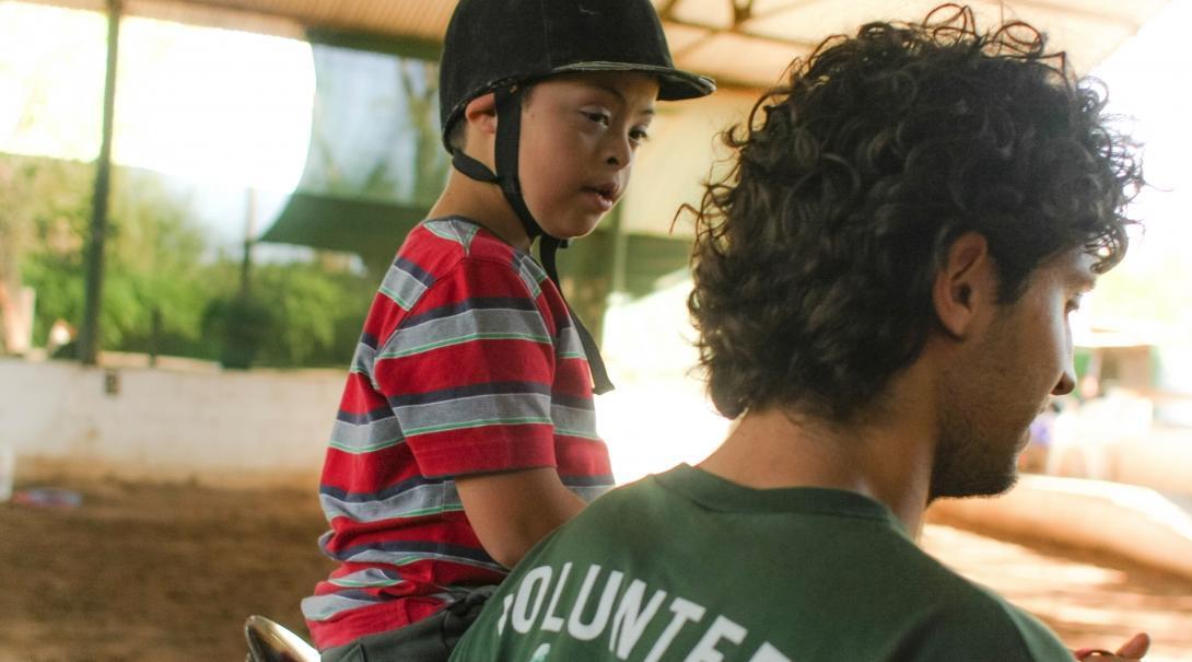 Un voluntario acompaña a un niño durante su sesión de equinoterapia en Argentina.